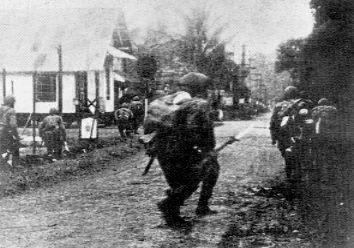 Japanese paratroopers carefully advancing through the streets of Menado, January 1942